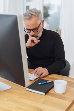 Thoughtful businessman sitting staring at his keyboard as he works at a desktop computer in the office