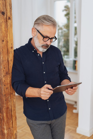 Man with a beard and glasses standing leaning against an interior wooden pillar reading a tablet pc