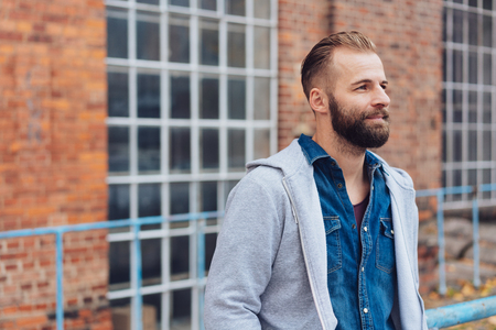 Bearded man standing deep in thought staring ahead with a contemplative expression standing in front of a brick commercial building