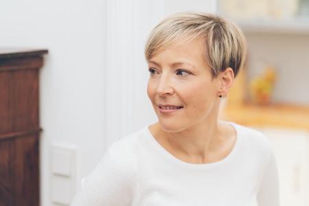 Attraktive blonde Frau, die mit einem nachdenklichen Lächeln in einem Nahaufnahmekopf- und Schulterporträt zur Seite schaut