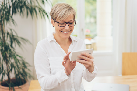 Happy woman scrolling through photos or the internet on her mobile phone with a beaming smile of pleasure
