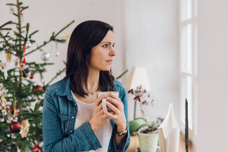 Woman with cup of tea standing against Christmas tree at home Stock Photo