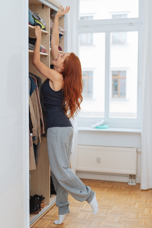 Young woman stretching to reach her clothes in a wardrobe in a walk in closet balancing on tip toe