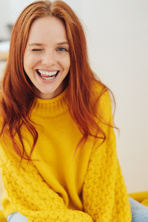 Sassy attractive young redhead woman winking playfully at camera with her tongue between her teeth Standard-Bild