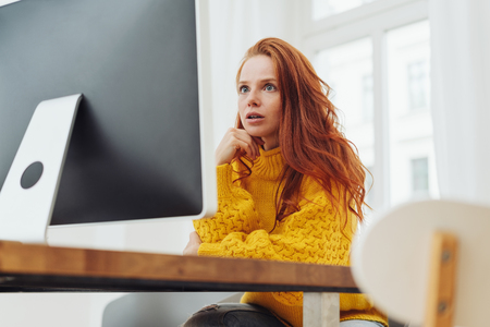 Young woman staring at her desktop monitor with a look of fascination and concentration inn a low angle view