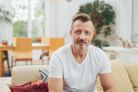 Good looking middle age man in white t-shirt sitting on the couch in living room and looking at camera. Front half-length portrait with copy space