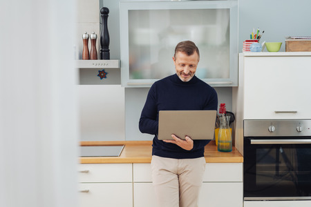 stylish man using a laptop computer in a kitchen standing leaning against the counter balancing it on his arm with a smile