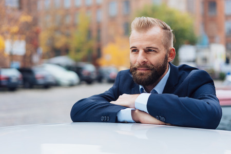 A young, entrepreneurial business man contemplates while leaning on a car roof in an urban scene.