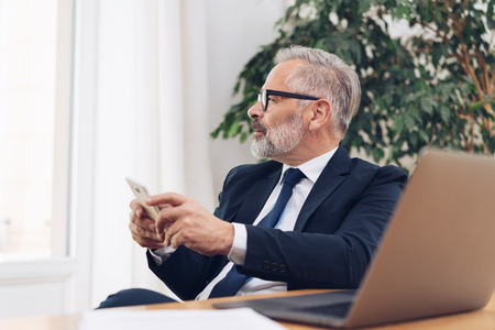 Middle-aged grey-haired bearded man in business suit and glasses, sitting with smartphone in hands and laptop on the desk in office, looking away at the window