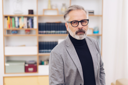 Good looking middle-aged grey-haired bearded man in black sweater and grey blazer, in black glasses. Front half-length indoors portrait against bookshelf blurred in background Stok Fotoğraf