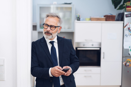 Businessman standing thinking in his house leaning on the door frame holding a mobile phone looking to the side