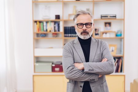 Grey-haired middle-aged man with beard, wearing grey blazer and black glasses, standing with arms crossed against the rack in background, looking at camera with no emotions. Half-length front portrait Banco de Imagens