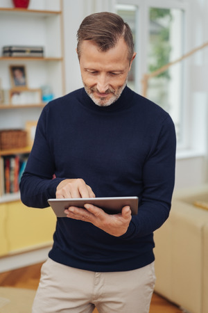 Adult man in black turtleneck using tablet pc, standing in living room interior and looking at the screen