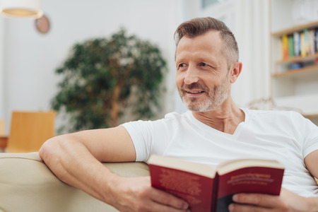 Bust front portrait of adult man in white t-shirt and with short stylish haircut, reading book at home, sitting on couch in living room. Looking away at the side of copy space Фото со стока