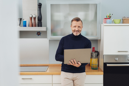 Front half-length portrait of happy adult man in dark sweater with tablet pc in his hands, leaning back on kitchen counter, looking at camera and smiling Zdjęcie Seryjne