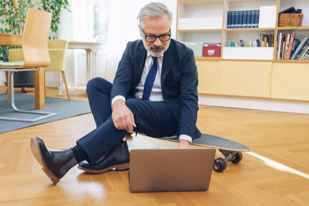 Sporty businessman working sitting on a skateboard on the parquet floor of his living room in his suit using a laptop computer