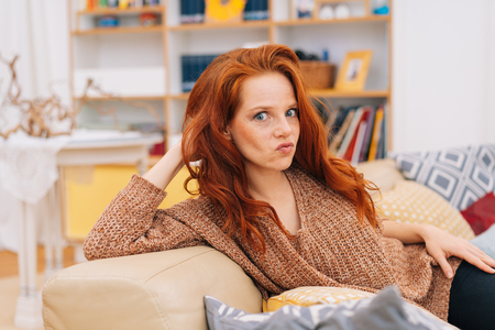 Young woman pulling a face of disgust looking wide eyed at the camera with puckered lips and a grimace while relaxing on a comfortable sofa at home Stock Photo