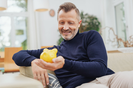 A relaxed, smiling mature man reclining on a couch ay home with a yellow piggy bank in a financial concept.