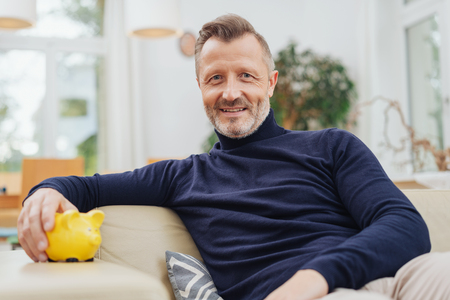 A relaxed mature man reclining on a couch ay home with a yellow piggy bank in a financial concept.