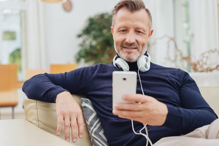 Middle-aged man relaxing listening to music on his mobile phone with stereo headphones around his neck 스톡 콘텐츠 - 115108928