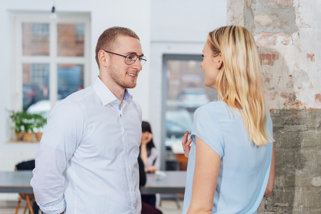 Casual young businesswoman talking to a male colleague who is smiling as he listens to her Banco de Imagens - 115702560