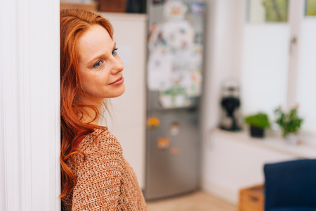 Young dreamy woman in sweater and with red hair leaning back on doorjamb and looking away. Close-up side portrait with home kitchen is blurred in background, copy space