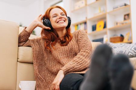 Gelukkige vrouw ontspannen thuis met koptelefoon luisteren naar muziek Stockfoto