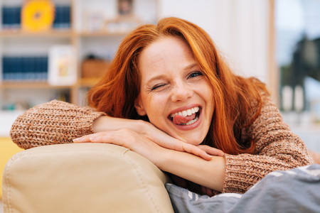 Mischievous woman winking at the camera with her tongue out as she relaxes on a sofa at home in a close up view