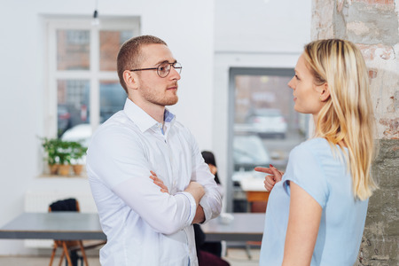 Businesswoman and man having a serious discussion as they stand facing one another in an office