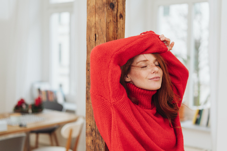 Dreamy young woman standing with her eyes closed and a serene blissful smile as she raises her hands above her head leaning on a pillar indoors Фото со стока - 115810235