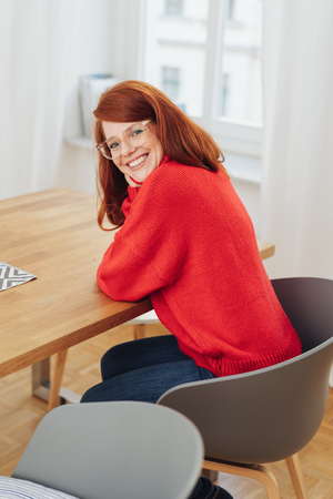 Smiling redhead woman wearing glasses seated in a tub chair at a table turning to smile happily at the camera
