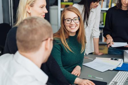 Attraktive lächelnde junge Geschäftsfrau mit Brille, die mit einem männlichen Kollegen in einem Meeting mit einem zufriedenen Lächeln plaudert