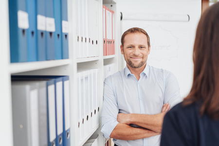Happy confident businessman chatting with a co-worker leaning with folded arms against shelves of office binders smiling widely at her