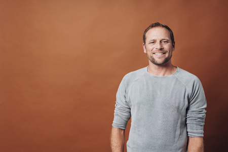Half-length front portrait of gladly smiling handsome young man in grey long sleeve shirt, standing against brown background with copy space, and smiling at camera