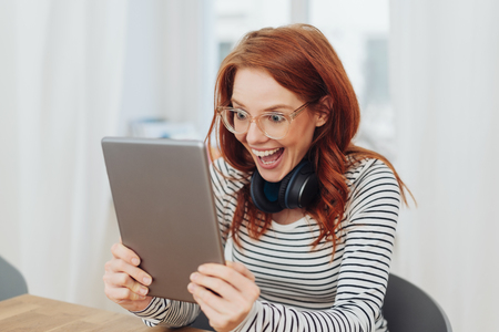 Excited young woman with a gleeful expression staring wide eyed at a handheld tablet computer with an elated smile 스톡 콘텐츠