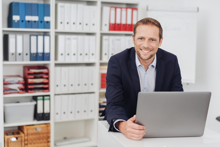 Front half-length portrait of friendly smiling businessman sitting in office interior with laptop and looking at camera, as if welcoming or listening client. Successful business concept, copy space Stok Fotoğraf