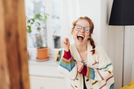Very happy cute young girl with pigtails singing or screaming, standing in the room in white sweater and glasses. Front half-length portrait with copy space