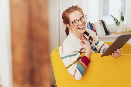 Happy friendly young woman wearing glasses and her red hair in a braid relaxing in a yellow armchair with a tablet turning to smile at camera