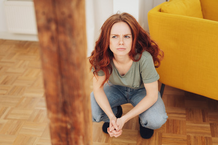Puzzled young woman crouching down thinking with a serious expression and frown indoors on a parquet floor in her living room Banco de Imagens