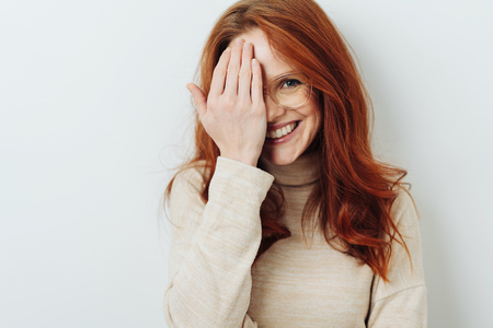 Smiling attractive redhead woman wearing glasses covering one eye with her hand isolated on white