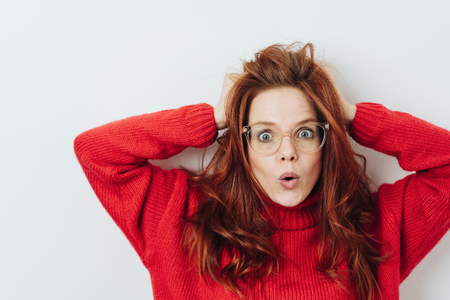 Astonished young woman staring wide eyed at the camera pursing her lips and running her hands through her long red hair