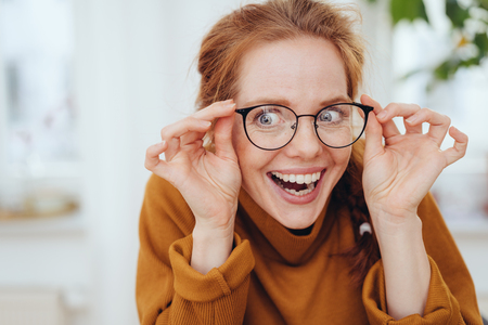 Surprised girl in orange sweatshirt touching glasses on her face with side smile and bulging eyes. Close-up portrait with copy space