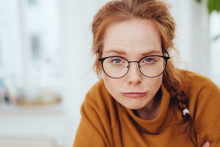 Funny portrait of a pretty red-haired girl in glasses and orange sweatshirt, making questioning look grimace, while looking at camera with a smirk. Close-up portrait with copy space