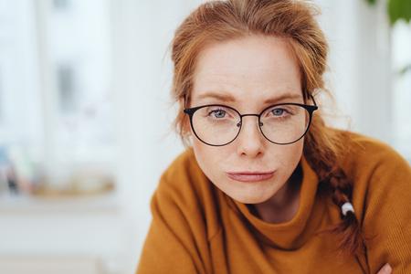 Lustiges Porträt eines hübschen rothaarigen Mädchens in Brille und orangefarbenem Sweatshirt, das fragende Grimasse aussehen lässt, während es mit einem Grinsen in die Kamera schaut. Nahaufnahmeportrait mit Kopienraum Standard-Bild