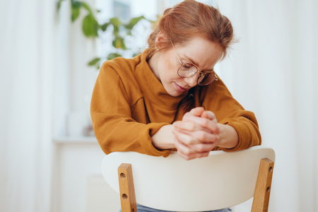 Beautiful young red-haired woman in glasses with thoughtful look sitting backwards on chair with her hands together, looking down and thinking or dreaming Banco de Imagens