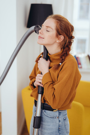 Blissful young housewife hugging a vacuum cleaner by the handle with her eyes closed and a peaceful smile after completing the housework