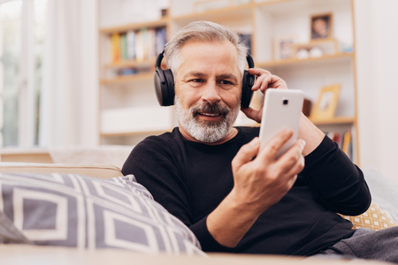 Senior bearded man relaxing listening to music on a sofa at home using his mobile phone and stereo headphones in a close up low angle view