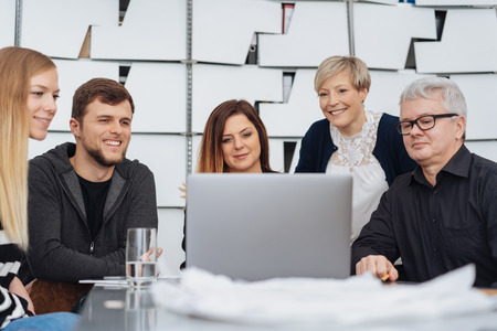 Group of business colleagues brainstorming together around a laptop computer in a modern office in a low angle view across the table