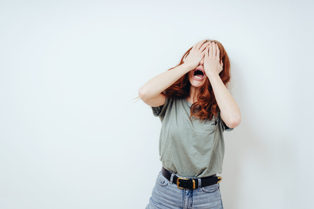 Anguished young woman covering her eyes wailing against a white wall with copy space