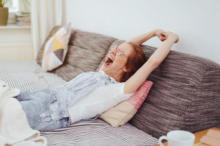 Mujer joven relajada relajándose en una cama de día con una alfombra sobre sus piernas estirando sus brazos y bostezando ampliamente
